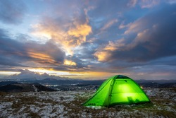 Tent on the top of the mountain against the backdrop of the sunset