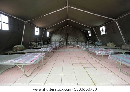 Tent Shelter With Temporary Beds Ready for Disaster Refuges #1380650750