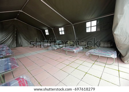 Tent shelter with temporary beds ready for natural disaster refuges #697618279