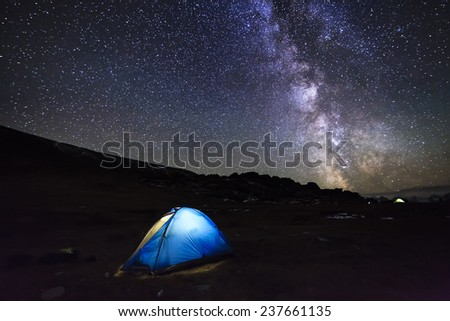 Tent with travelers in the mountains on the background of the magical starry sky.