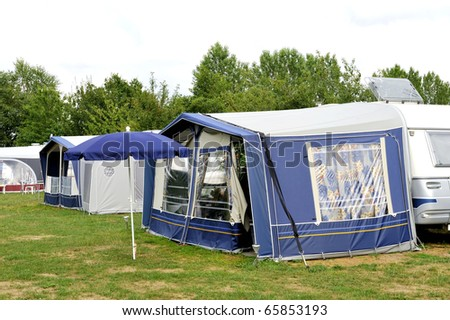 Tents and a caravan at a camping site. NO PEOPLE