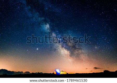 Tents glowing under the milky way at night. Camping in the mountains under the starry magical sky. 5 Billion Star Hotel. Foto stock ©