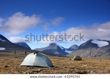 Tents in the Arctic mountains of Sweden, with blue sky and beautiful white clouds.