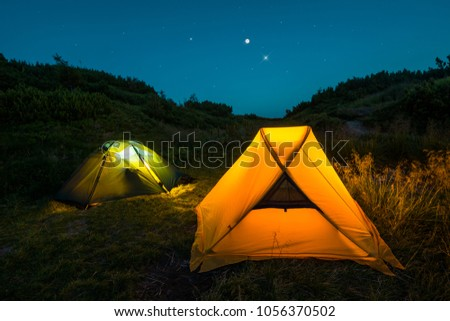Tents under night starry sky, camping. Overnight in the forest, among wild nature. #1056370502