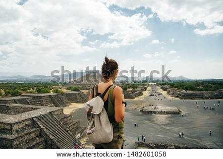 Teotihuacan, Mexico. A Mexican American tourist with a backpack and hat enjoys the view from the top of the Moon Pyramid. The Sun Pyramid and Avenue of the Dead can be seen in the distance.