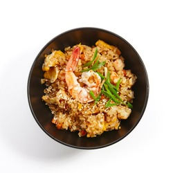 Teppanyaki Fried rice with shrimp vegetables fresh herbs and seasonings in dark bowl on white isolated background. Pan-Asian cuisine in restaurant. Top View