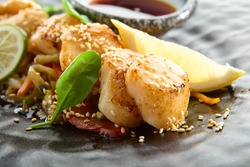 Teppanyaki Style Scallop - Grilled Sea Scallop with Soy Sauce and Vegetables. Japanese Teppanyaki Scallop garnished with lemon and fresh basil leaf. Black asian plate closeup view