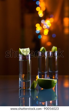 tequila and lime on a glass table.