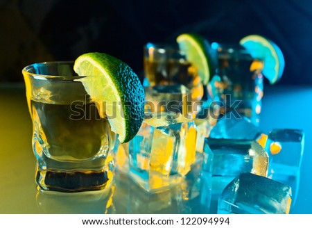tequila , lime and ice on a glass table.