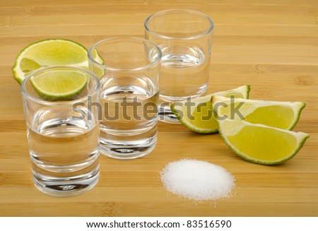 tequila, lime and salt on a wooden background - stock photo