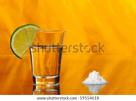 Tequila shot with a half a slice of lime on the glass and a pile of salt by the side on orange background (Selective Focus)