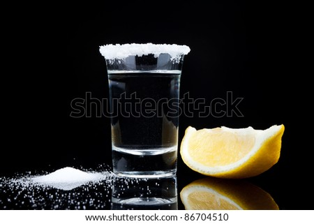 tequila shot, with lemon and salt close up on black background