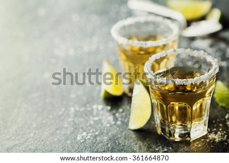 Tequila shot with lime and sea salt on black table, selective focus