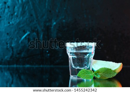 Tequila shot with lime, salt and mint against black background with blue light #1455242342