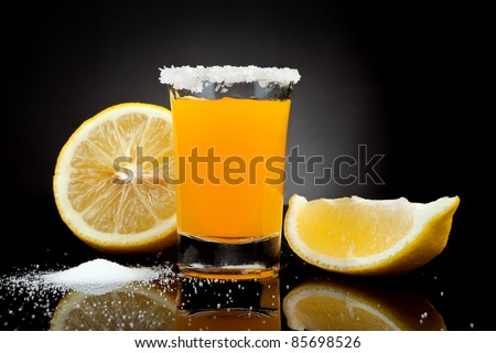 tequila shot with salt and lemon on black background