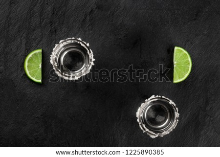 Tequila shots with lime slices, shot from above on a dark background with a place for text #1225890385