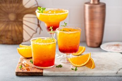 Tequila sunrise margarita cocktail in different glasses with ice, refreshing summer drink
