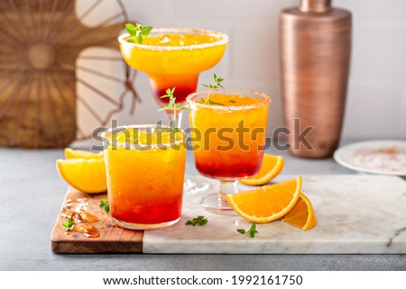 Tequila sunrise margarita cocktail in different glasses with ice, refreshing summer drink Foto stock ©