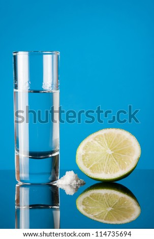 Tequila with lime and salt on a blue background