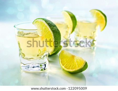 tequila with lime on a white reflective background.