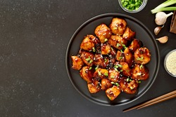 Teriyaki chicken on plate over black stone background with free text space. Top view, flat lay