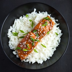 teriyaki salmon and  rice, served with sesame seeds and chopped green onions, top view.