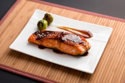 Teriyaki salmon plate on bamboo mat. Japanese cuisine inspired dinner consisting of a grilled salmon fillet glazed in delicious teriyaki sauce (soy sauce base). Healthy brussel sprouts as sides.