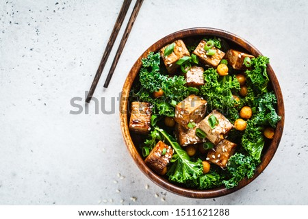 Teriyaki tofu salad with kale and chickpeas in wooden bowl. Сток-фото ©