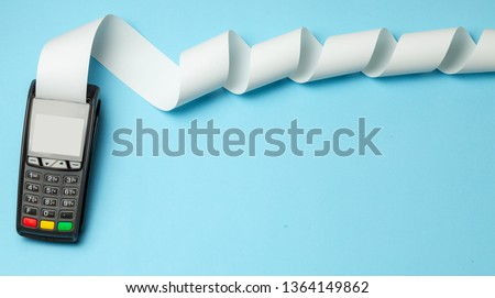 Terminal cash register machine POS for payments and long roll cash tape on blue background. Copy space for text