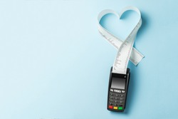 Terminal cash register machine POS for payments and long roll paper cash tape in heart shaped on blue background. Copy space for text