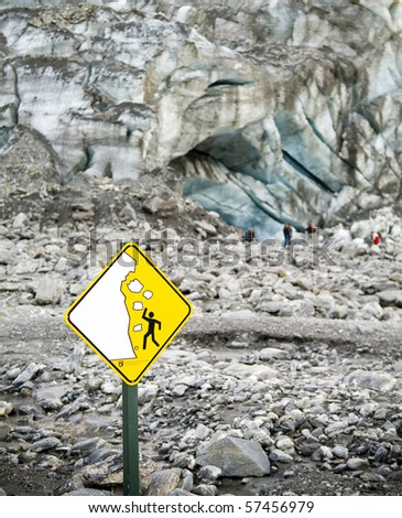 Terminal face of a glacier with a warning sign and people ignoring it