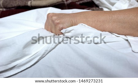 Terminally-ill woman clenching bedsheets feeling terrible pain, death convulsion