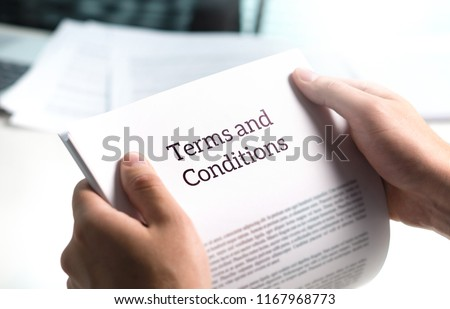 Terms and conditions text in legal agreement or document about service, insurance or loan policy. Lawyer or client holding contract paper in office.