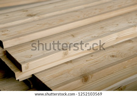 Terrace boards larch with strips, building materials in warehouse. Unpainted grooved wood terrace planks in stack.
