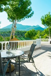 Terrace by the pool of luxurious white villa with chairs table fascinating view of valley mountains covered with green trees on sunny summer day. Vacation holiday escape tranquility