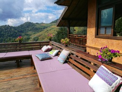 Terrace corner with beautiful scenery of nature and it is decorated with long comfortable cushion seat and pillows and flower pot on wooden backrest