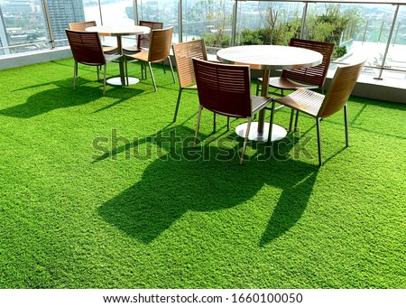 Terrace, Cushion made of fabric and furniture outdoor table set. Placed on an artificial green grass, table set for dining decorating with artificial grass circle shape on the floor.