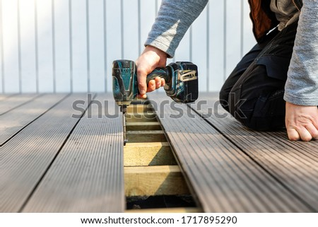 terrace deck construction - man installing wpc composite decking boards Stock photo ©