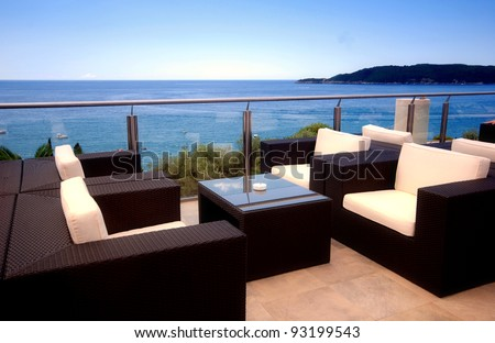 Terrace lounge with rattan armchairs and sea view in a luxury resort .