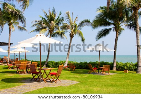 Terrace of a restaurant with white sun shades on a beautiful beach