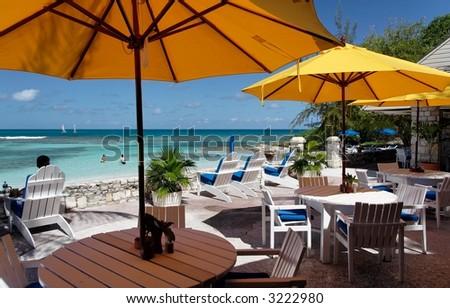 Terrace of a restaurant with yello sun shades on a beautiful caribbean beach - stock photo