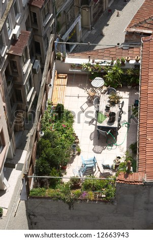 Terrace on the roof with green garden and flowers