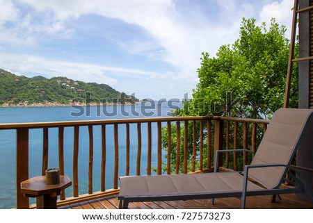 Terrace or balcony seating for looking at paradise sea view, blue sky with sofa beach chair, small wooden table and ashtray. concept of summer beach,Holiday, Relaxation and vacation. Koh Tao, Thailand #727573273