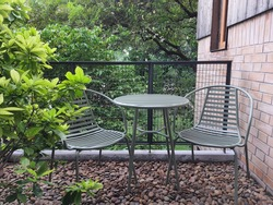 Terrace with green leaves tree, chairs and table for relaxing, brick and Yakisugi (burned wood) wall