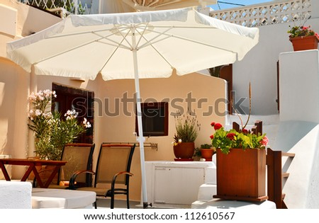 Terrace with sunshade  decorated  flowers on Santorini, Greece.