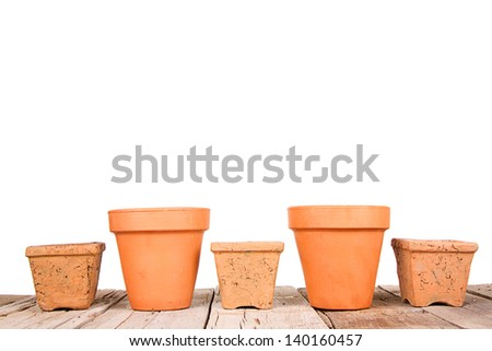Terracotta or clay gardening pots on a wooden plank on a white background