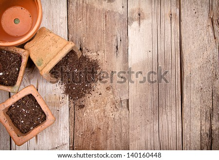 Terracotta or clay gardening pots with dirt spilling out of a pot, on a wooden background