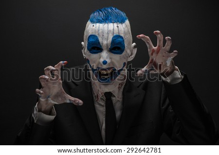 Terrible clown and Halloween theme: Crazy blue clown in black suit isolated on a dark background in the studio