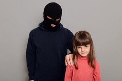 Terrible criminal man wearing black hoodie and robber mask holds a little preschool girl hostage, stands and holds child by the shoulder, kidnapping, isolated on gray background.