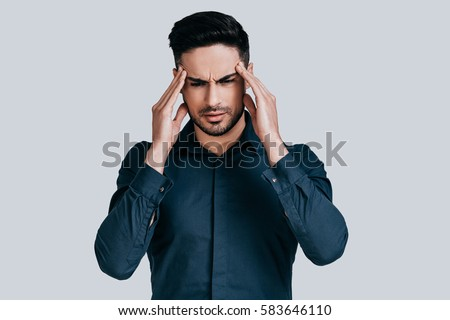 Terrible headache. Frustrated young man touching his head with hands and making face while standing against grey background #583646110